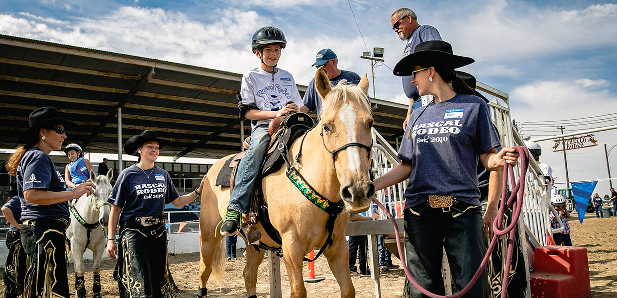 child on a horse in the rodeo arena